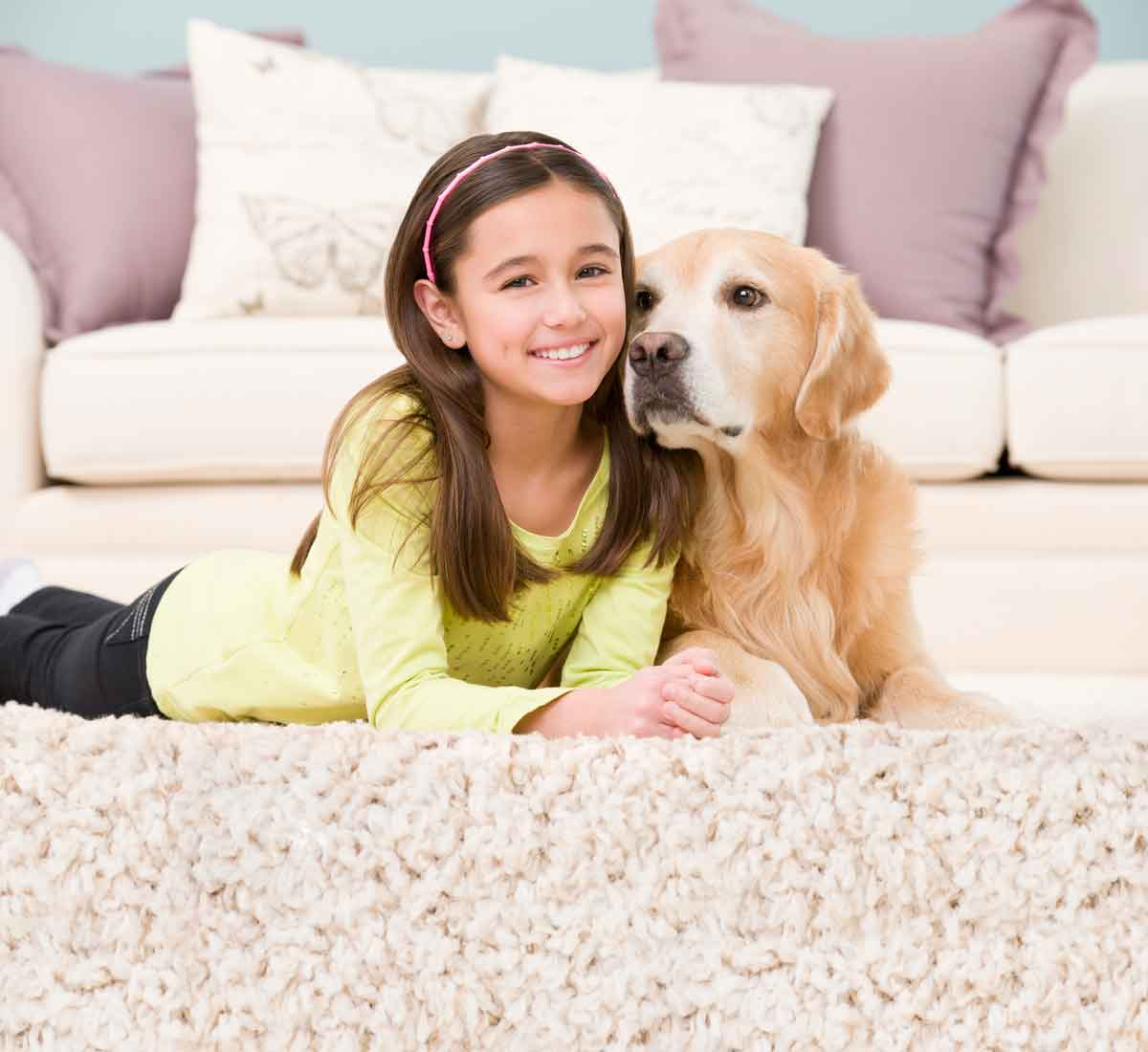 Girl and dog sitting on rug in Minneapolis, MN home