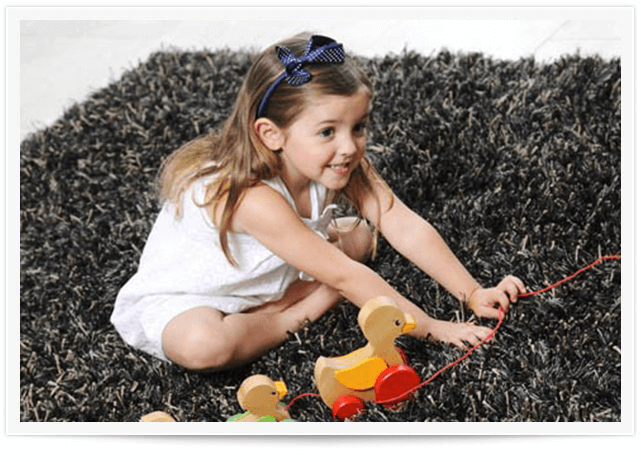 girl playing with toys on gray area rug