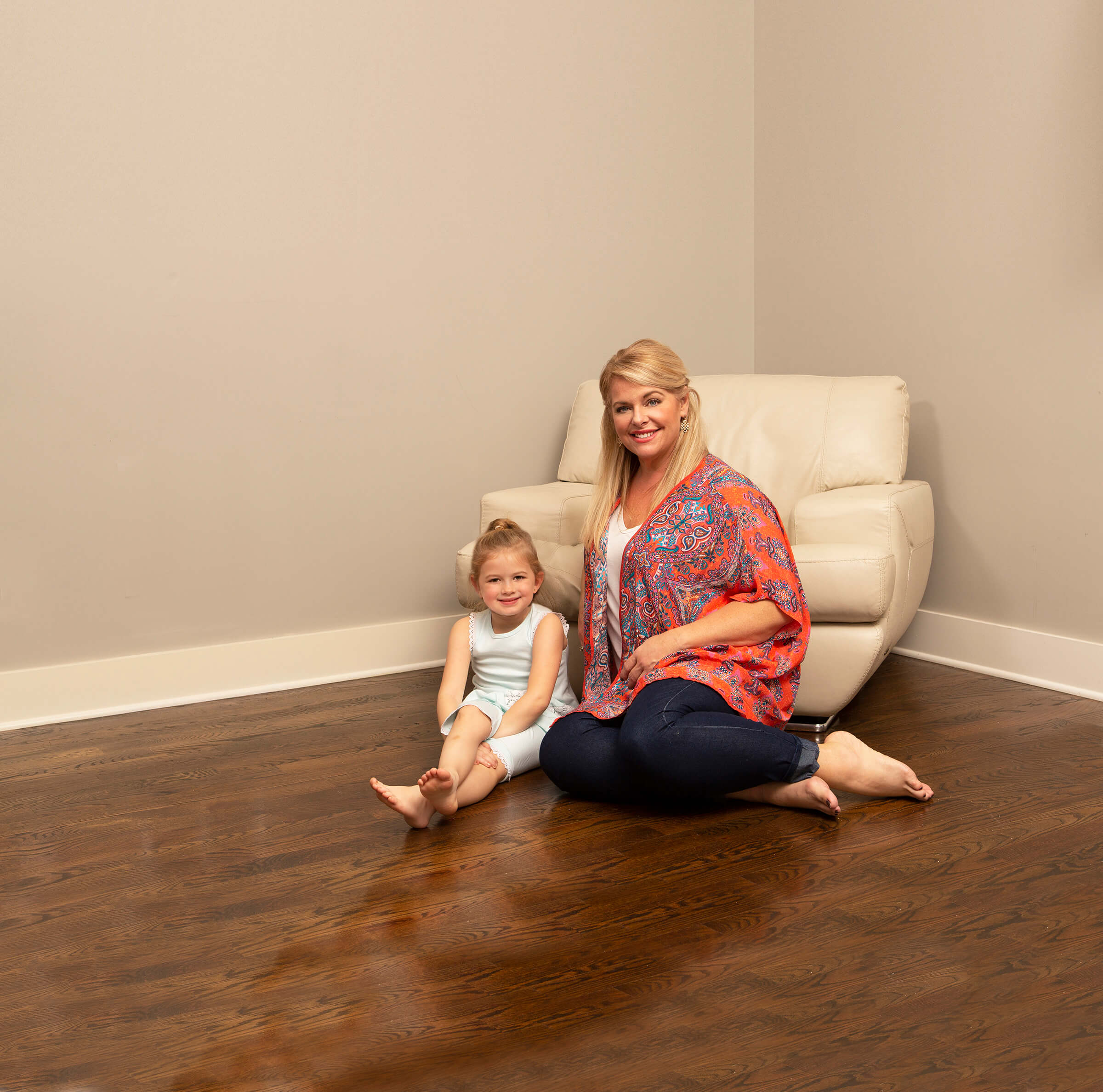 Mother and daughter sitting on clean wood floor in Anoka, MN
