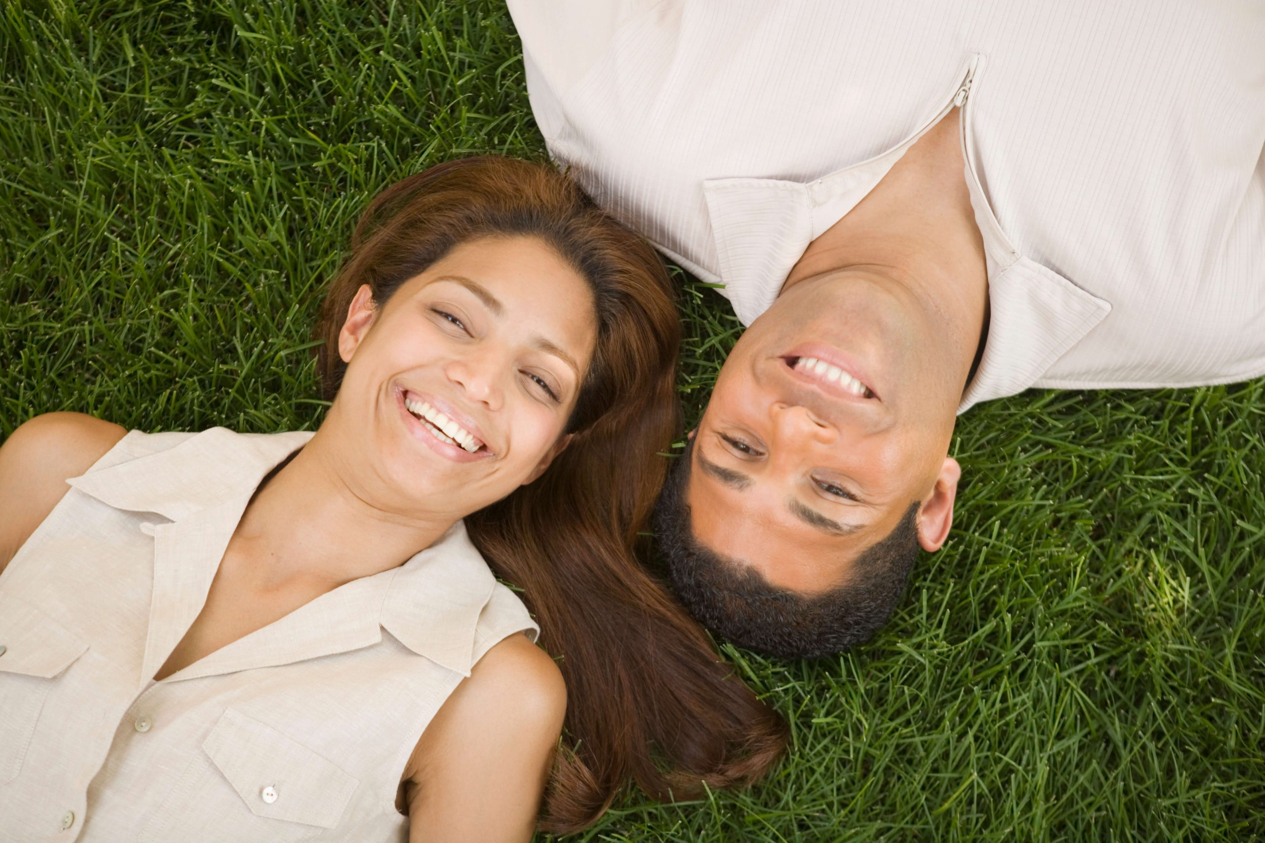 Couple laying on green grass in Minneapolis