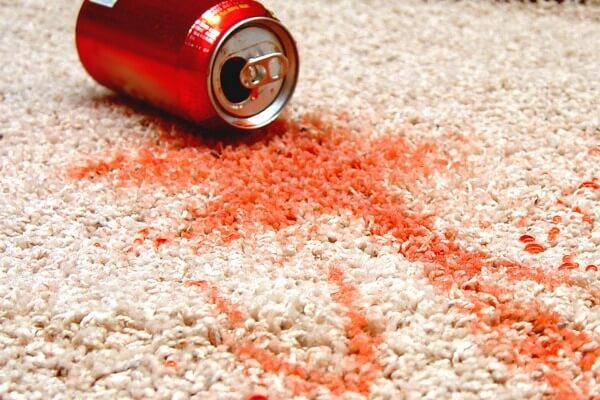 Red soda stain on white carpet